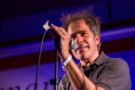 Mann mit Mikrofon auf einer Bühne.
