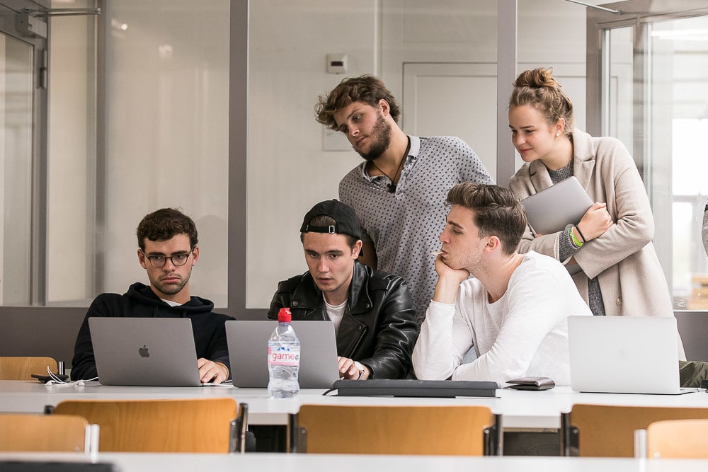Studentengruppe arbeitet an einem Computer.