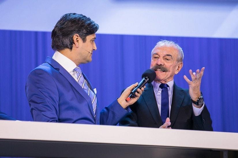 Moderator führt ein Gespräch mit einem Mann.