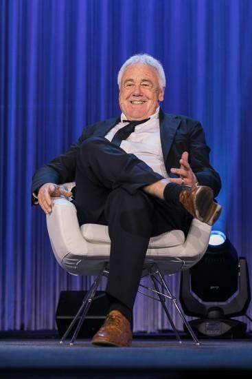 Mann sitzt in einem weissen Stuhl.