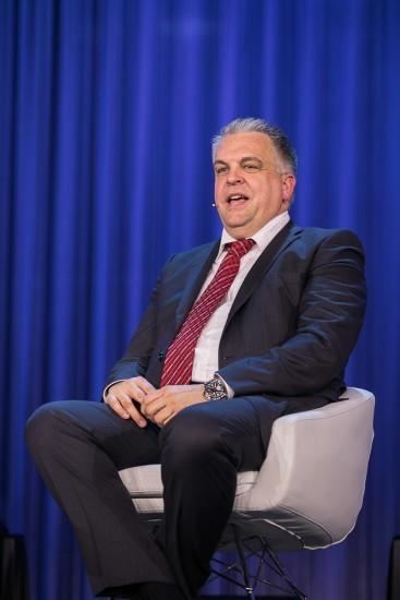 Mann mit roter Krawatte sitzt in einem Stuhl.