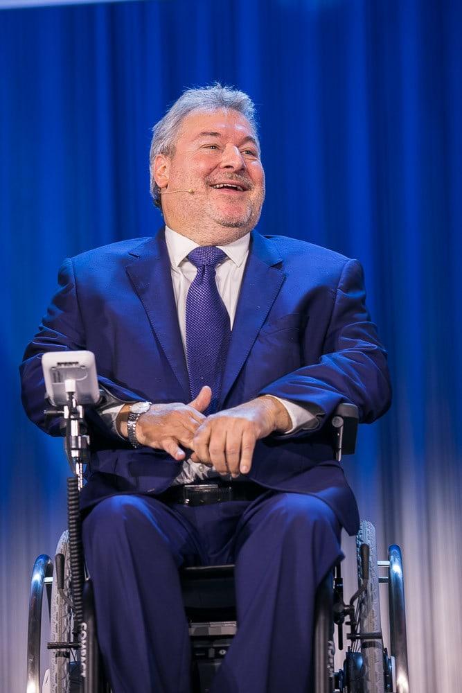 lachender Mann in einem Rollstuhl.