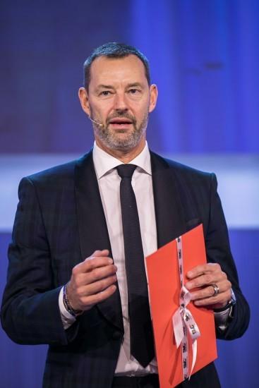 Mann mit einem roten Umschlag auf der Bühne