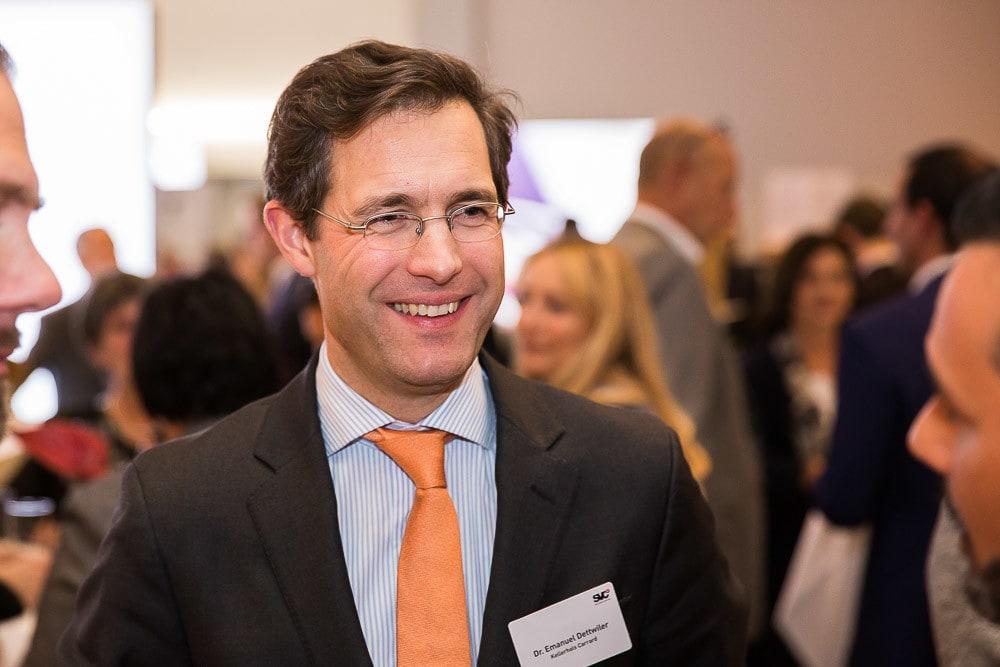 Mann mit oranger Krawatte.