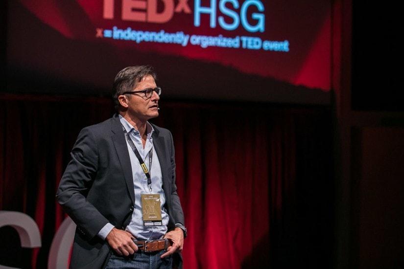 Mann auf der Bühne, im Hintergrund das TED Logo.