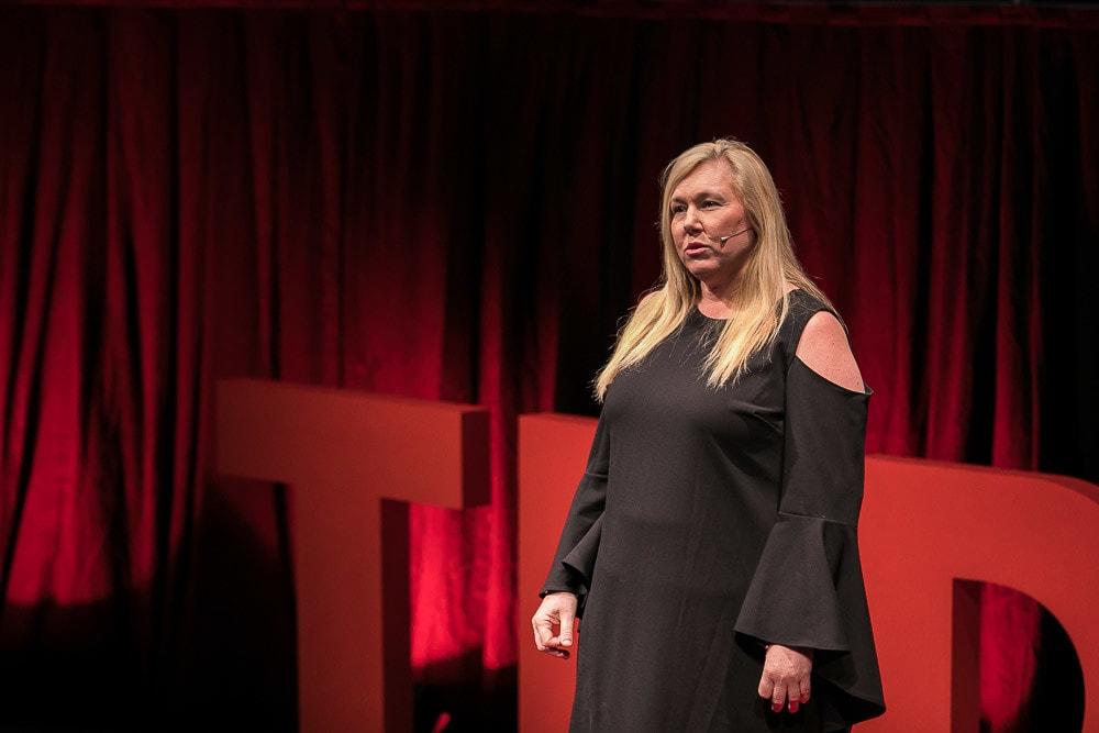 schwarz gekleidete Frau namens Rosanne Stuart auf der Bühne, im Hintergrund das TEDx Logo.