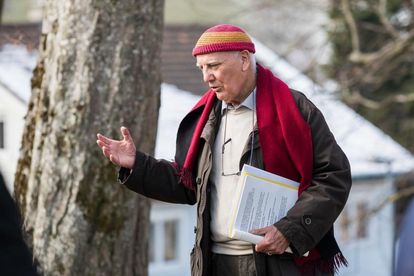 Mann referiert vor einem Baum.