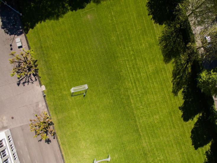 Fussballplatz von oben, grüner Rasen mit weissem Tor.