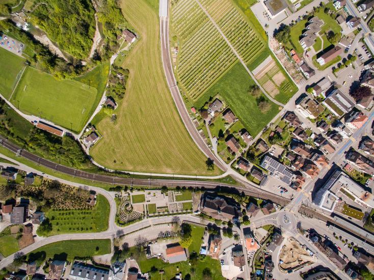 Blick von oben auf Felder, Häuser und Bahnlinie.