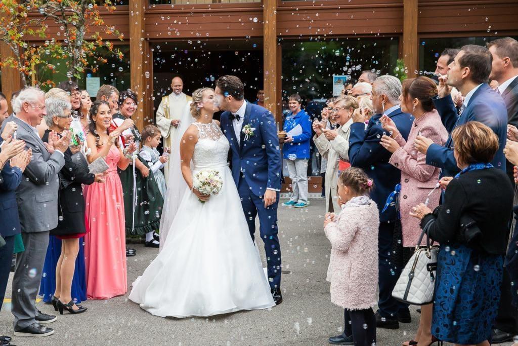 Brautpaar küsst sich vor Kapelle umringt von Leuten welche Seifenblasen pusten.