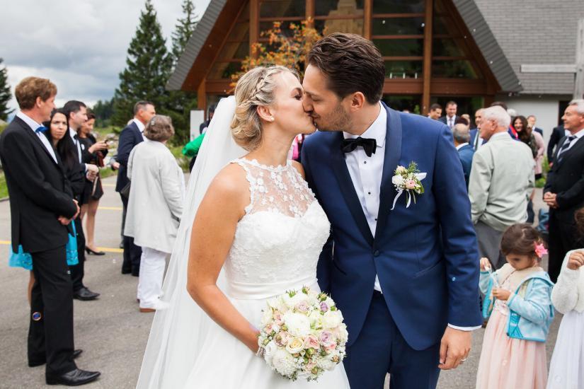 Brautpaar küsst sich vor der Kapelle.