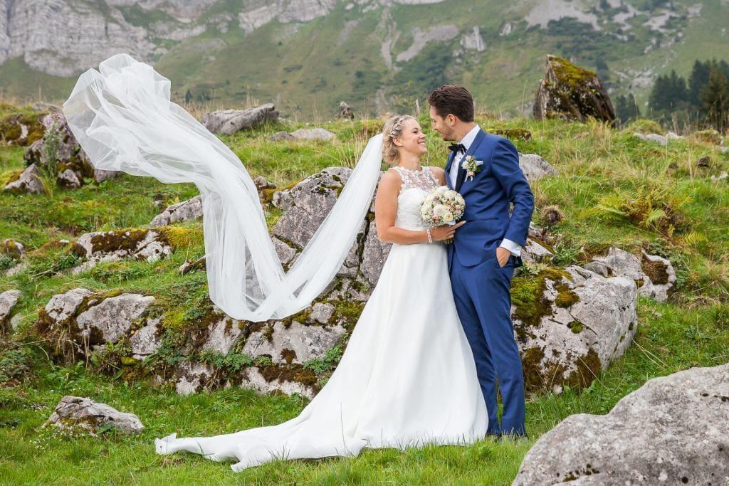 Brautpaar mit im Wind wehendem Schleier.
