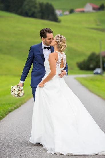 schönes Braupaar beim küssen, Mann hält den Brautstrass.
