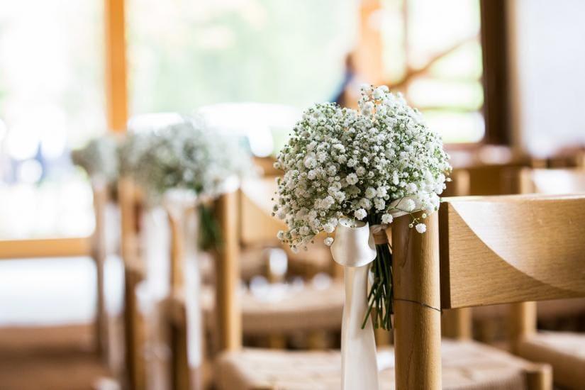 Hochzeitblumendeko an einem Stuhl.
