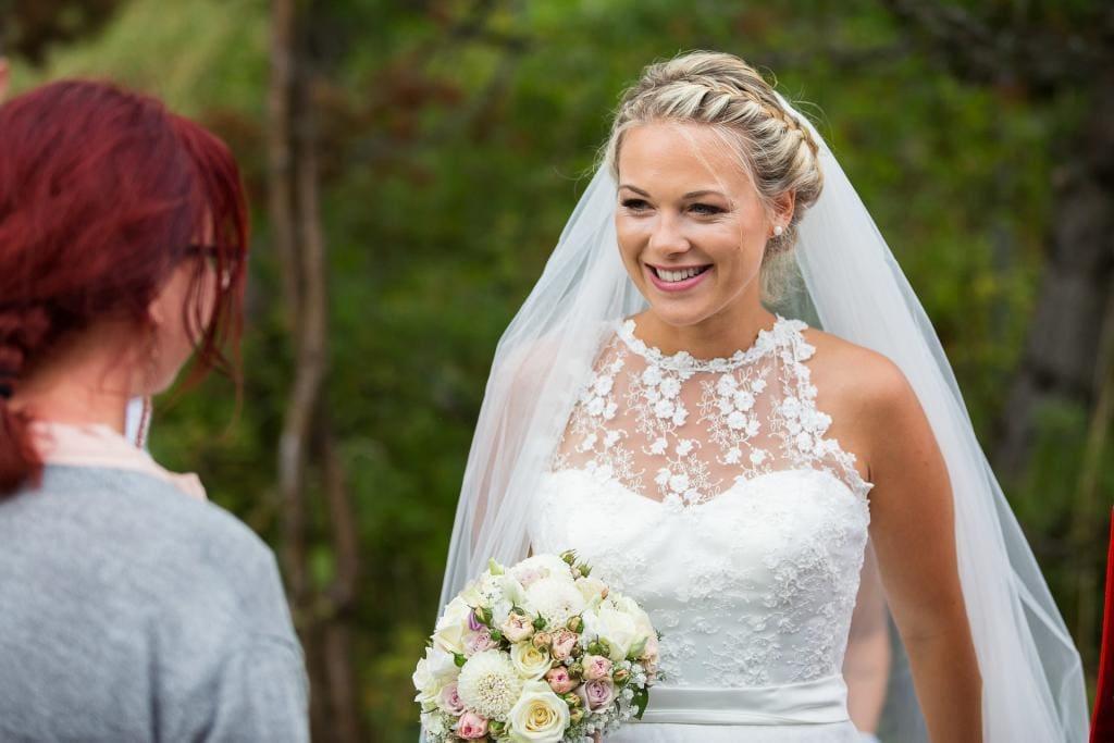 Lachende Braut mit Brautstrauss.