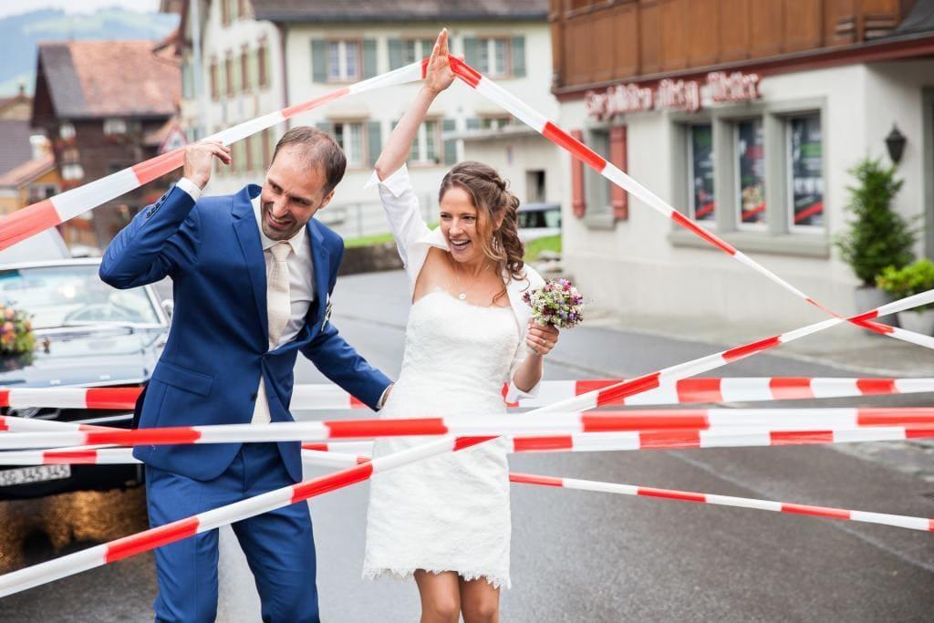 Hochzeitspaar muss durch Absperrband klettern.