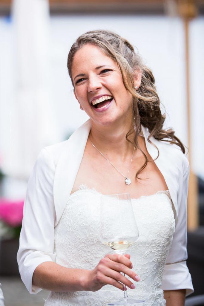 lachende Braut mit Weinglas.
