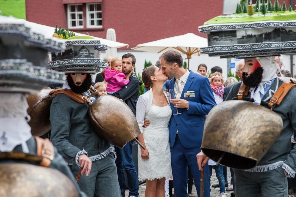 Hochzeitspaar küsst sich zwischen Silvesterchläusen.