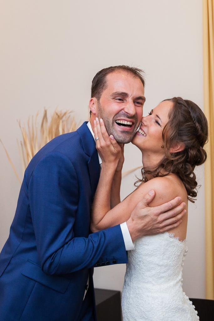 Braut küsst Mann im Standesamt.