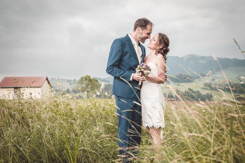 Hochzeitspaar küsst sich im hohen Gras.