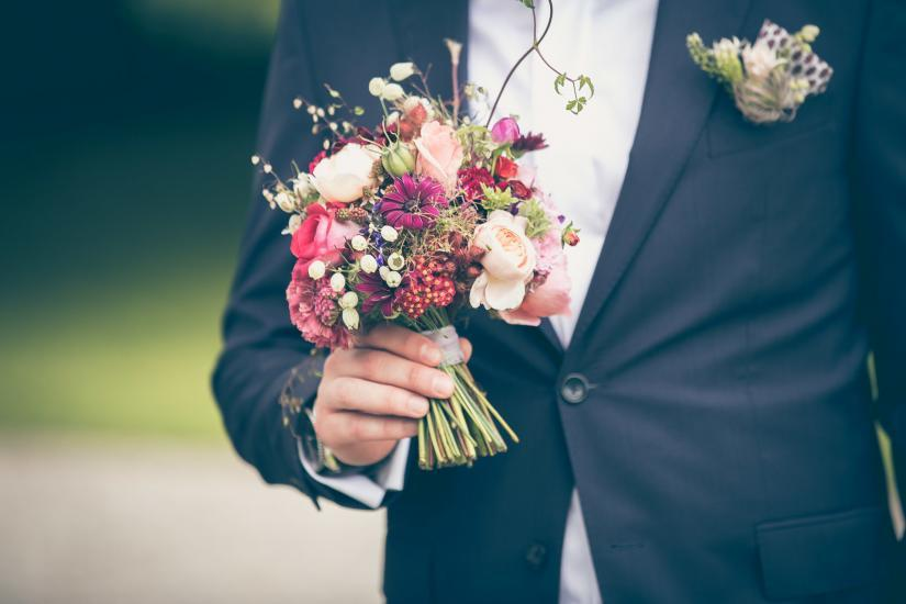 Bräutigam hält Brautstrauss