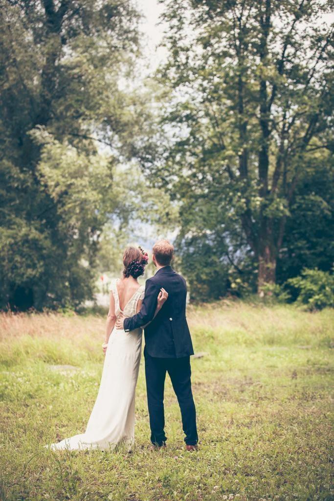Brautpaar steht in der grünen Natur.