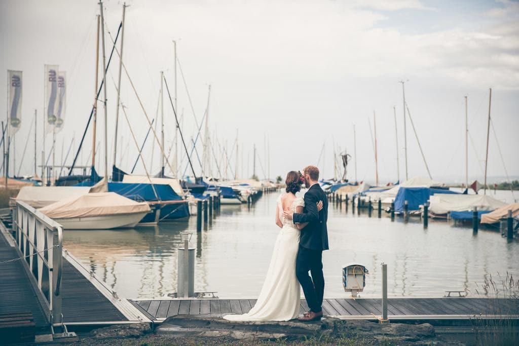 Brautpaar steht im Hafen vor ein paar Segelbooten.