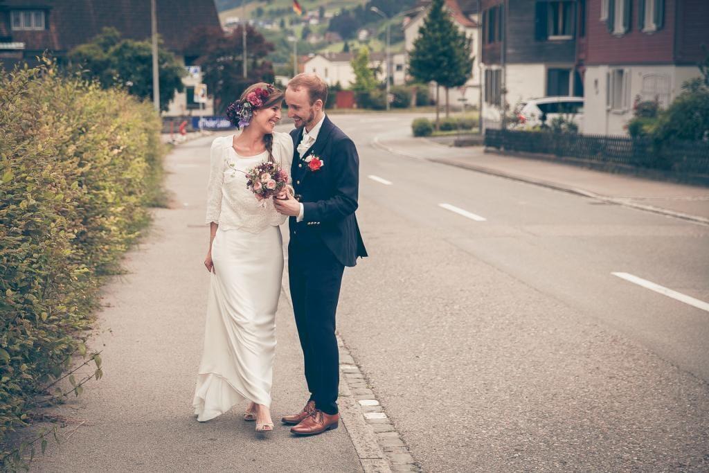 Brautpaar steht lachend am Stassenrand.
