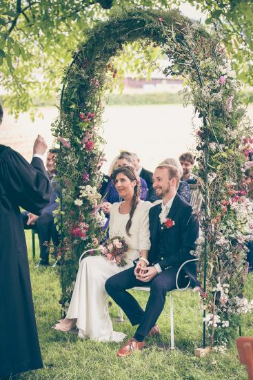 Brautpaar unter Blumenbogen bei der Zeremonie.
