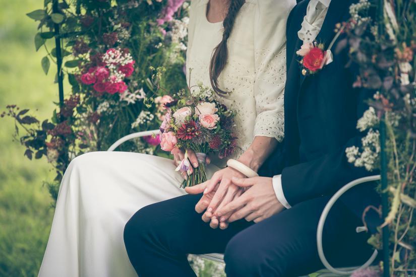 Nahaufnahme von Händen und Blumen.
