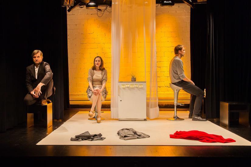eine Frau und zwei Männer sitzen auf einer Bühne