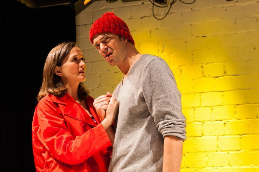 Frau mit rotem Mantel und Mann mit roter Mütze halten sich die Hände