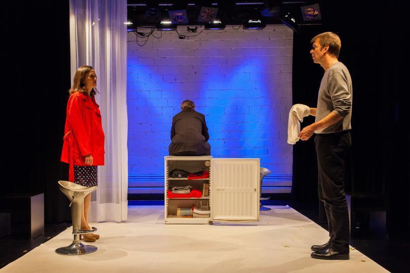 drei Personen auf einer Bühne mit offenem Kühlschrank