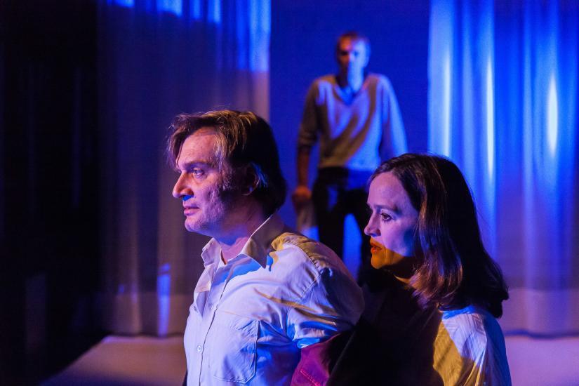 dunkle melancholische Theaterszene mit drei Personen