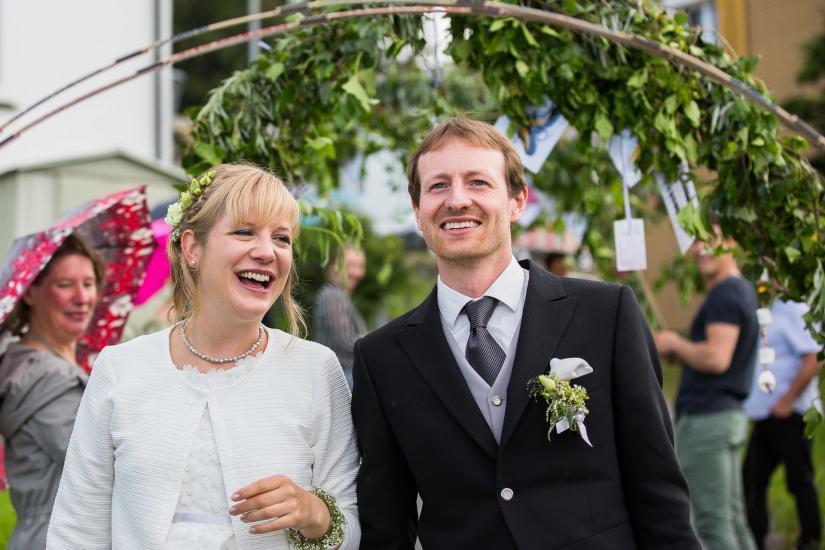 fröhliches Brautpaar unter Spalier