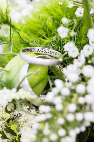 Makrofotografie zweier Hochzeitsringe auf einem grün weissen Brautstrauss
