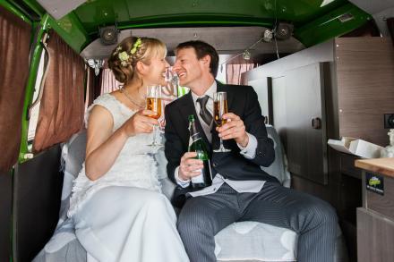 Hochzeitspaar sitzen in einem VW-Bus und trinken Champagner
