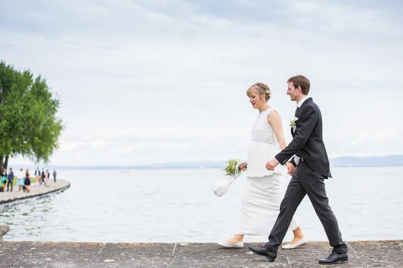 Brautpaar läuft am Bodensee entlang