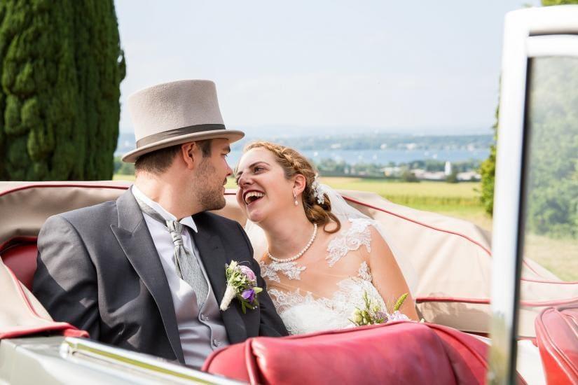Brautpaar sitzt in einem Oldtimer.