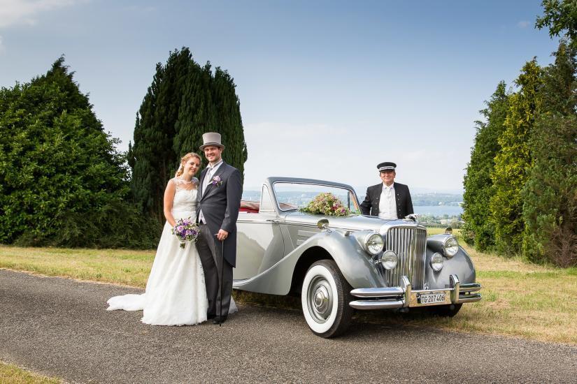 Brautpaar steht vor einem Oldtimer mit Chauffeur.
