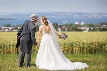 Brautpaar küsst sich vor einem Kornfeld. Im Hintergrund sieht man den Bodensee.