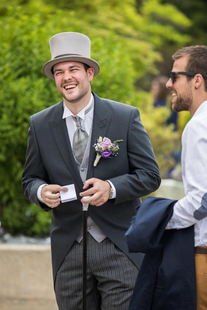 Lachender Bräutigam steht vor der Kirche.