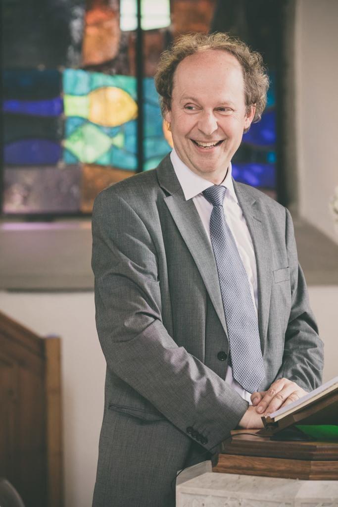 Fröhlicher Pfarrer bei einer Trauung.