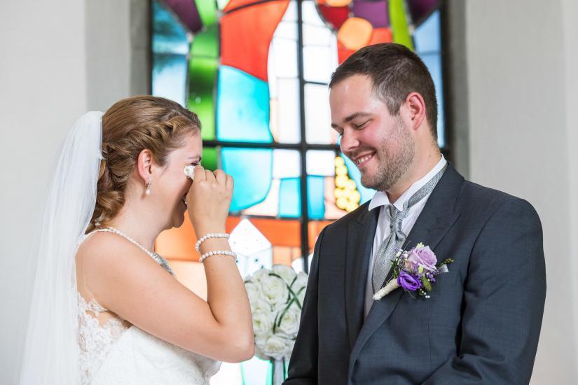 Brautpaar in der Kirche, Braut tupft sich Tränen ab.