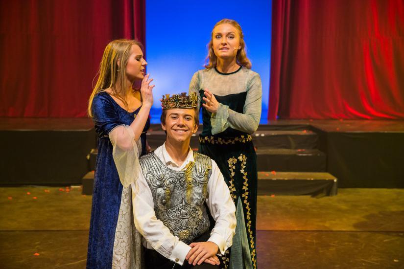 Zwei Frauen krönen den Prinzen.