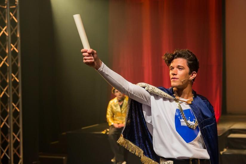 König hält eine Papierrolle in die Luft.