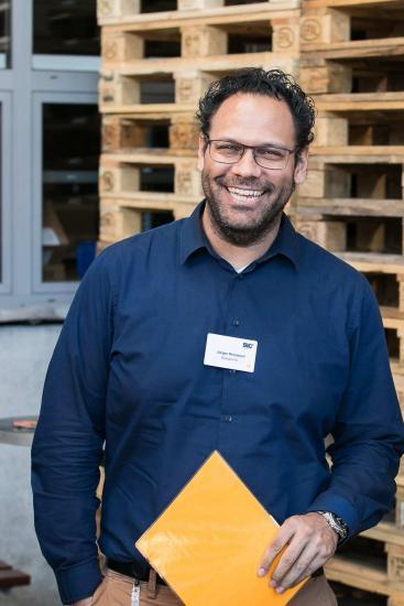 lachender Mann mit blauem Hemd und Brille.