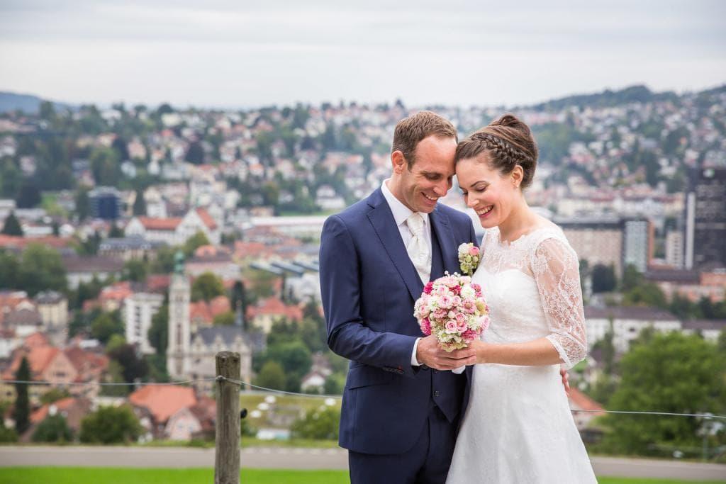 lachendes Brautpärchen betrachten den Brautstrauss.