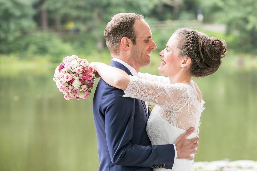 Fröhliches Brautpaar umarmt sich.