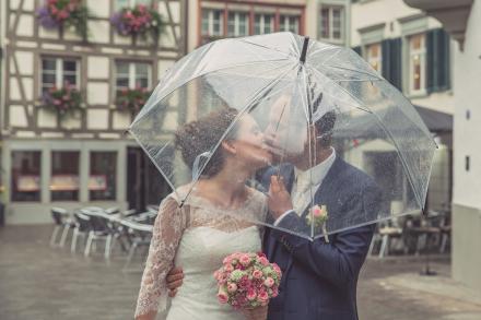 Brautpaar küsst sich hinter einem durchsichtigen Regenschirm in der Altstadt von St.Gallen.